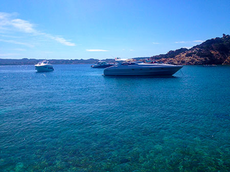 Yachts and power boats stop in the clear blue waters of La Maddalena archipelago. Sardinia